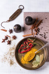 Spices tumeric and dry reh hot chili peppers on metal plate, srved over white tablecloth with vintage weight. Top view