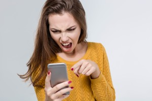 Portrait of angry woman screaming on the phone isolated on a white background