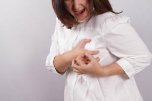 woman clutching her chest. in pain, possible heart attack