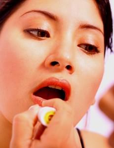 Young Woman Making Herself Beautiful By Applying Lipstick