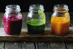 Assortment of vegetable smoothies from carrot, beetroot and spinach in glass jars. Over old wooden table. Dark rustic style, natural day light