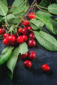 Branch of fresh cherries with leaves on black background