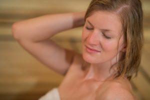 Closeup of young woman sweating in sauna