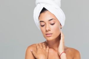 Portrait of a pretty woman with towel on head posing on gray background