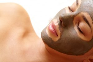 Relaxed girl having pore cleaning mask in isolation