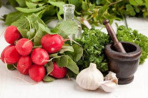Bunch of fresh radishes with garlic, parsley and vintage mortar on white table